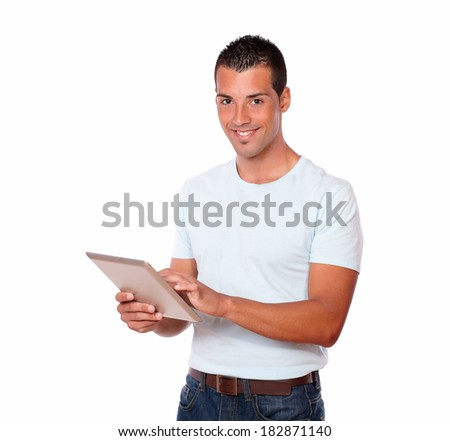 Portrait of an attractive hispanic man on white t-shirt and jeans using his tablet pc while standing and smiling at you on isolated studio