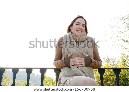 Portrait of an attractive hispanic middle aged mature woman in a home garden, relaxing by a balcony with countryside views, joyful and smiling at camera with space, outdoors. - stock photo
