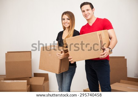 Portrait of an attractive Hispanic young couple moving into their new apartment and smiling