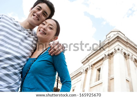 Portrait of an attractive Japanese tourist couple visiting London city and laughing and hugging while standing next to a classic museum gallery building during a sunny day on holiday, outdoors.