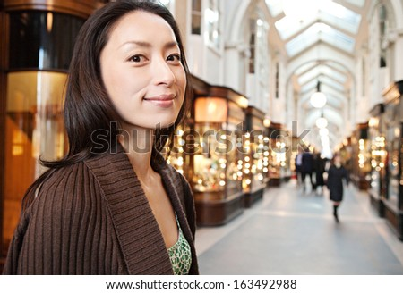 Portrait of an attractive Japanese tourist woman smiling and visiting a shopping mall in the city of London while on a holiday break trip, with stores and lights in the background. - stock photo
