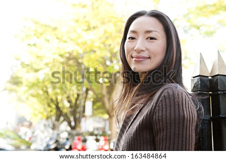 Portrait of an attractive Japanese tourist woman visiting the city of London during a sunny day and standing near a park with black railings, smiling and looking at camera while turning, outdoors. - stock photo
