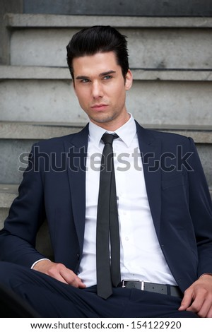 Portrait of an attractive male fashion model sitting on stairs - stock photo