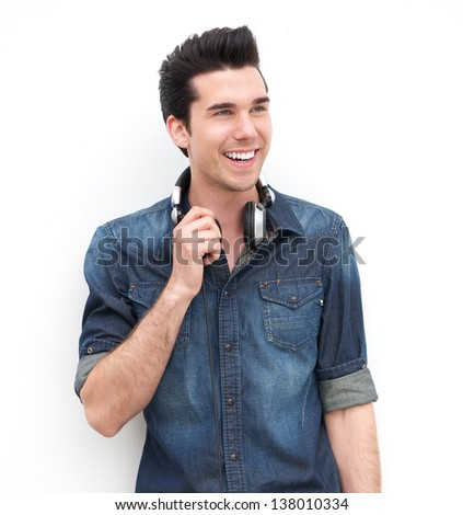 Portrait of an attractive male fashion model standing with headphones - stock photo