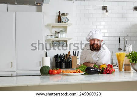 Portrait of an attractive mature chef with hat on the head leaning on big kitchen table and looking to the camera - stock photo