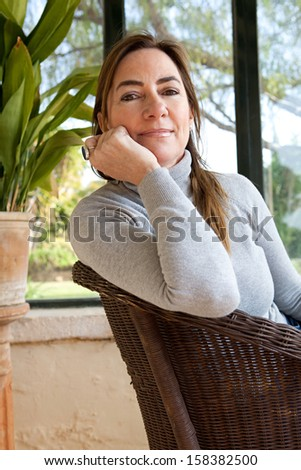 Portrait of an attractive mature woman sitting in a home interior with large glass windows and a green garden, lounging and relaxing while smiling at the camera, indoors. - stock photo