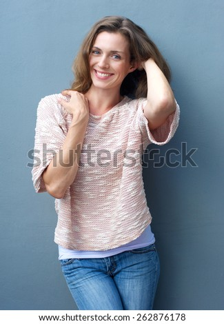 Portrait of an attractive mid adult woman smiling with hand in hair - stock photo