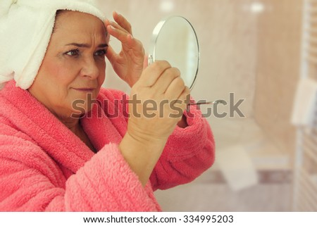 Portrait of an attractive middle aged woman looking into a mirror in the bathroom