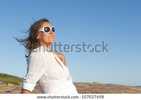 Portrait of an attractive middle aged woman, smiling and relaxed, wearing white blouse and sunglasses, isolated with blue sky as background and copy space. - stock photo
