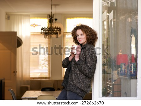 Portrait of an attractive middle aged woman standing with cup of tea at home - stock photo