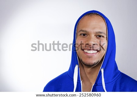 Portrait of an attractive mixed race man smiling to camera in a blue hooded jumper - stock photo