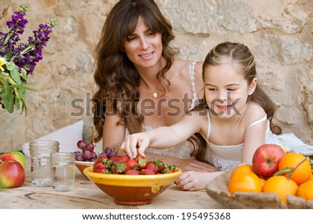 Portrait of an attractive mother and her young daughter eating fresh fruit in a holiday home outdoors, with the girl reaching to pick a strawberry. Healthy family lifestyle eating and living. - stock photo