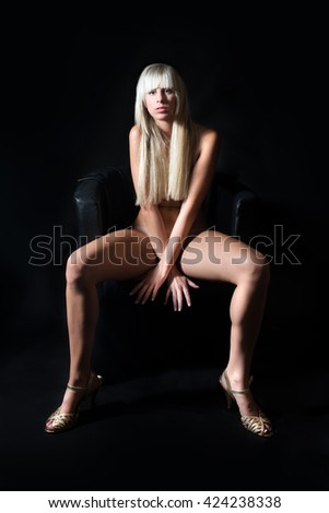 Portrait of an attractive nude blond woman on black armchair, all private parts covered by her hair and hands
