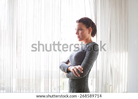 Portrait of an attractive office business woman being thoughtful in her home office desk against a large bright window, workplace interior. Professional woman looking confident and strong, indoors. - stock photo