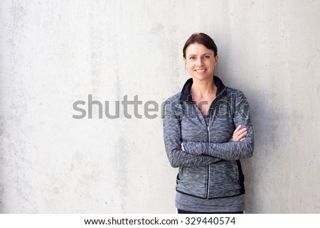 Portrait of an attractive older sports woman smiling against white wall - stock photo