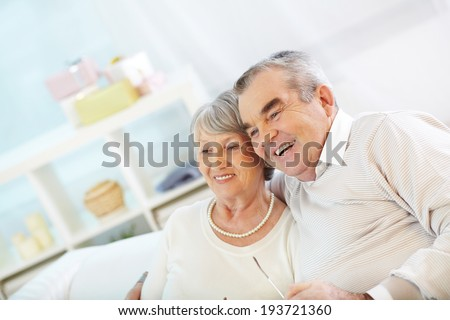 Portrait of an attractive senior couple watching TV - stock photo