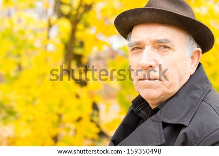 Portrait of an attractive senior man outdoors enjoying the sunshine in a stylish hat and overcoat against a backdrop of colourful yellow autumn trees with copyspace - stock photo