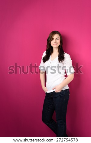 Portrait of an Attractive Smiling Girl, Wearing Casual Outfit, Leaning on a Pink Wall with Both Hands on Her Pockets and Looking at the Camera. - stock photo