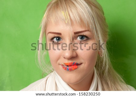 Portrait of an attractive smiling girl with lips in bright paints - stock photo