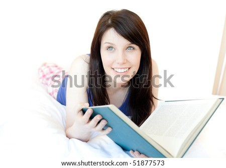 Portrait of an attractive teen girl studying lying on a bed against a white background - stock photo