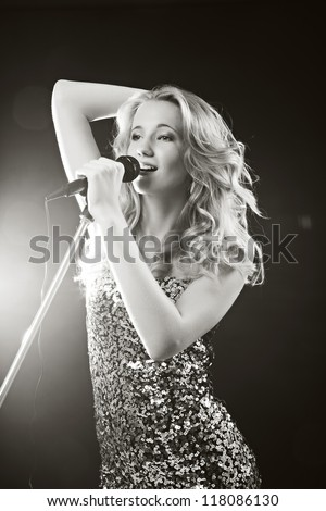 Portrait of an attractive teenager girl  singing with microphone. Black-white image - stock photo