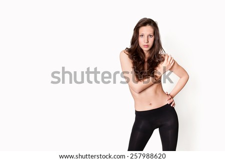 Portrait of an attractive topless model wearing black leggings in front of white studio background, photo with copy space on the left side of the image  - stock photo