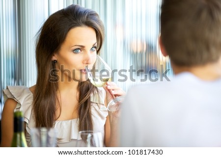 Portrait of an attractive woman drinking wine while on a date with her boyfriend - stock photo