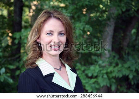 Portrait of an attractive woman in a business suit standing in a park. - stock photo