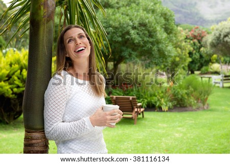 Portrait of an attractive woman laughing with cup of coffee outdoors  - stock photo