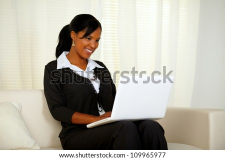 Portrait of an attractive woman on black suit working on laptop while sitting on couch at home indoor