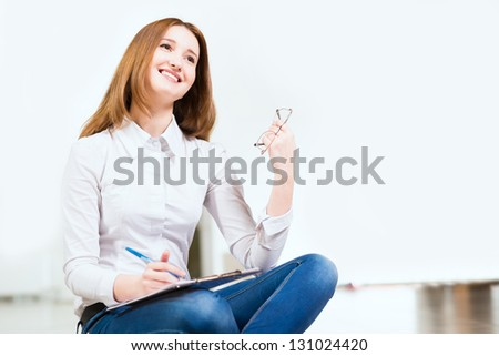 Portrait of an attractive woman sitting on the floor cross-legged and holds the tablet for notes - stock photo