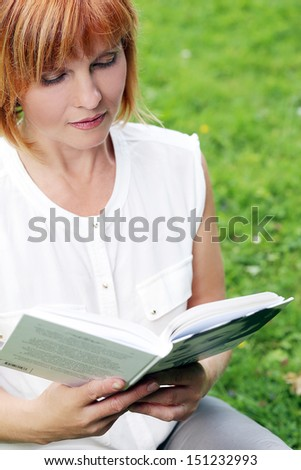 Portrait of an attractive woman who is relaxing at a park while reading a book