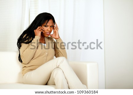 Portrait of an attractive woman with headache conversing on cellphone while sitting on couch at home indoor - stock photo