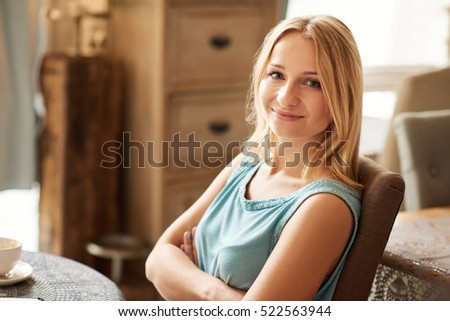 Portrait of an attractive young blonde woman smiling while sitting at a table at home drinking a coffee