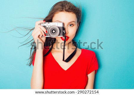 Portrait of an attractive young brunette woman in a red dress in the studio on a blue background with a camera in his hands - stock photo