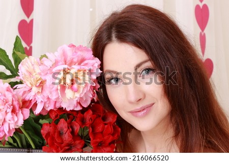 Portrait of an attractive young brunette woman with a bouquet of flowers in a romantic setting