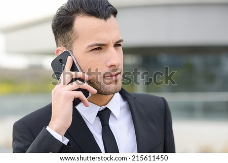 Portrait of an attractive young businessman on the phone in an office building