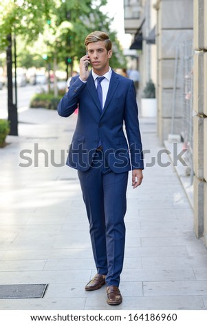 Portrait of an attractive young businessman on the phone in urban background, wearing blue suit and tie. Blonde hair - stock photo