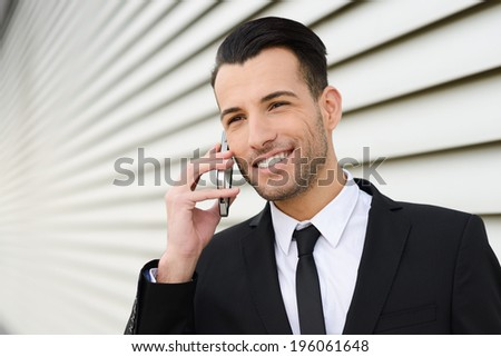 Portrait of an attractive young businessman smiling on the phone in an office building