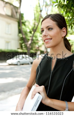 Portrait of an attractive young businesswoman holding a laptop computer under her arm while in a leafy street in the city with classic architecture.