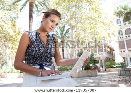 Portrait of an attractive young businesswoman using  laptop computer while sitting on a  bench in a classic city, outdoors.