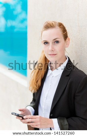 Portrait of an attractive young businesswoman with a smartphone - stock photo