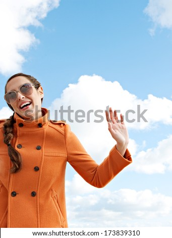 Portrait of an attractive young characterful woman waving hello or goodbye with her arm up smiling against a bright blue sky during a sunny day on vacation. Outdoor lifestyle. - stock photo