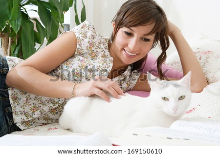 Portrait of an attractive young college student woman stroking her cat pet while laying on her bed at home with text books and studying for exams, smiling indoors bedroom. - stock photo