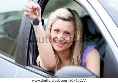 Portrait of an attractive young driver holding a key after buying a new car - stock photo