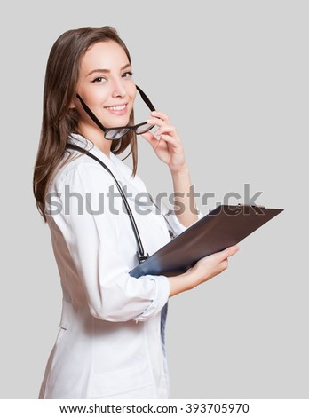 Portrait of an attractive young female doctor in white coat. - stock photo