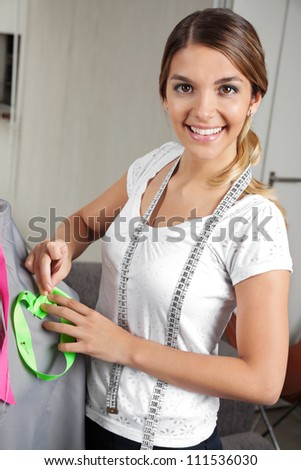 Portrait of an attractive young female fashion designer working on a mannequin with gray fabric - stock photo