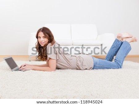 Portrait of an attractive young female lying on the carpet using a laptop - stock photo