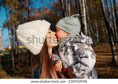 Portrait of an attractive young happy mother and her little son having fun in an autumn park. The boy kissing mother while on her arms - stock photo