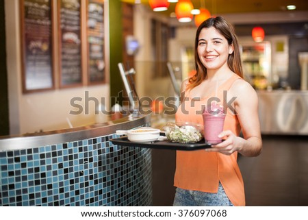 Portrait of an attractive young Latin woman holding a tray of healthy food at a restaurant - stock photo